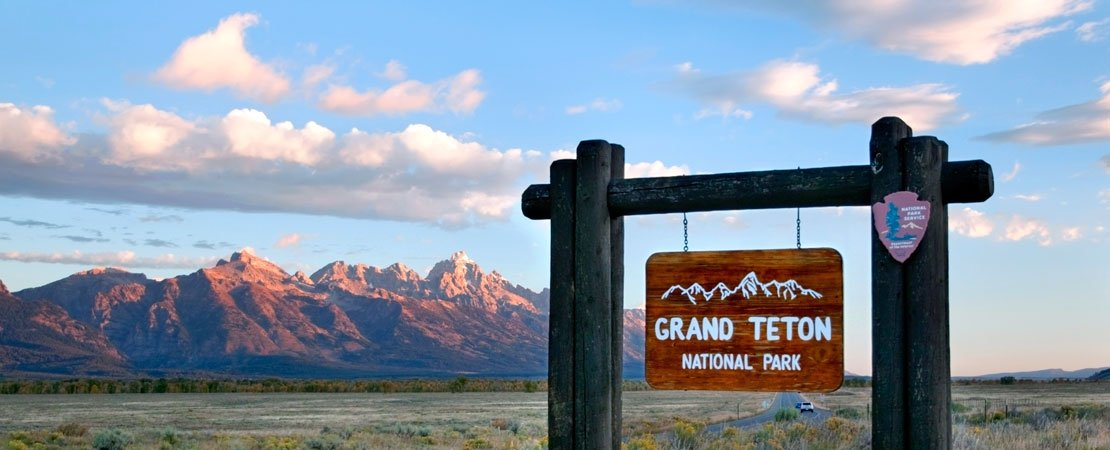 Grand Teton National Park sign in front of the Grand Tetons, Jackson Hole, Wyoming